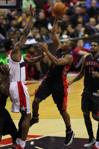 Feb 18, 2014; Washington, DC, USA; Toronto Raptors point guard Kyle Lowry (7) shoots the ball as Washington Wizards small forward Martell Webster (9) defends in the fourth quarter at Verizon Center. The Raptors won 103-93. Mandatory Credit: Geoff Burke-USA TODAY Sports