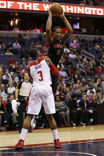 Feb 18, 2014; Washington, DC, USA; Toronto Raptors shooting guard DeMar DeRozan (10) passes the ball over Washington Wizards shooting guard Bradley Beal (3) in the fourth quarter at Verizon Center. The Raptors won 103-93. Mandatory Credit: Geoff Burke-USA TODAY Sports