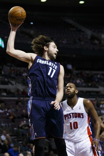 Feb 18, 2014; Auburn Hills, MI, USA; Charlotte Bobcats power forward Josh McRoberts (11) grabs the rebound over Detroit Pistons power forward Greg Monroe (10) in the third quarter at The Palace of Auburn Hills. Charlotte won 108-96. Mandatory Credit: Rick Osentoski-USA TODAY Sports