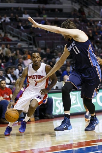 Feb 18, 2014; Auburn Hills, MI, USA; Detroit Pistons point guard Brandon Jennings (7) moves the ball defended by Charlotte Bobcats power forward Josh McRoberts (11) in the fourth quarter at The Palace of Auburn Hills. Charlotte won 108-96. Mandatory Credit: Rick Osentoski-USA TODAY Sports