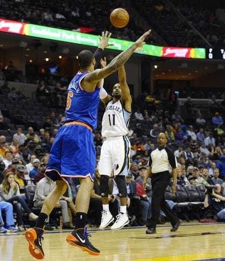 Feb 18, 2014; Memphis, TN, USA; Memphis Grizzlies point guard Mike Conley (11) shoots over New York Knicks center Tyson Chandler (6) during the game at FedExForum. Memphis Grizzlies beat New York Knicks 98 - 93. Mandatory Credit: Justin Ford-USA TODAY Sports