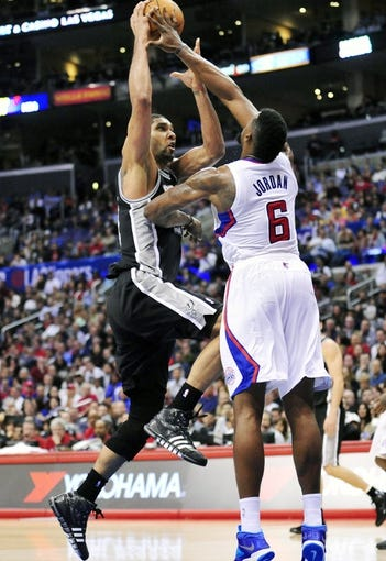 February 18, 2014; Los Angeles, CA, USA; San Antonio Spurs power forward Tim Duncan (21) moves to the basket against Los Angeles Clippers center DeAndre Jordan (6) during the second half at Staples Center. Mandatory Credit: Gary A. Vasquez-USA TODAY Sports