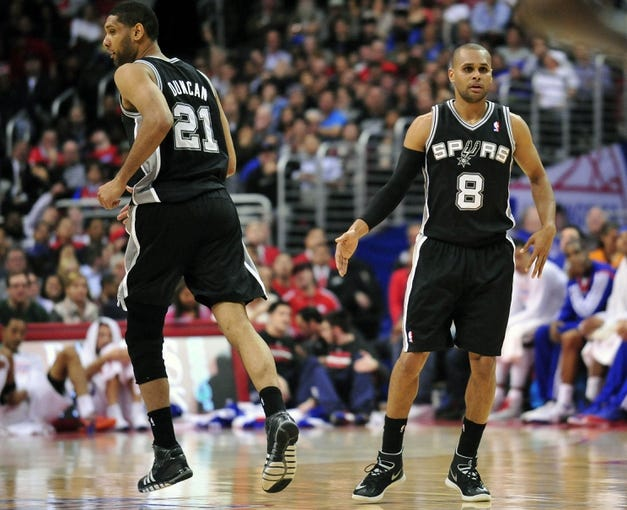 February 18, 2014; Los Angeles, CA, USA; San Antonio Spurs point guard Patty Mills (8) celebrates with power forward Tim Duncan (21) after scoring a basket against the Los Angeles Clippers during the second half at Staples Center. Mandatory Credit: Gary A. Vasquez-USA TODAY Sports