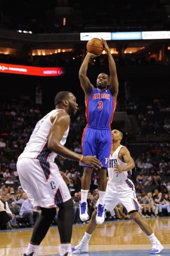 Feb 19, 2014; Charlotte, NC, USA; Detroit Pistons guard Rodney Stuckey (3) shoots as he is defended by Charlotte Bobcats center Al Jefferson (25) and guard Ramon Sessions (7) during the first half of the game at Time Warner Cable Arena. Mandatory Credit: Sam Sharpe-USA TODAY Sports