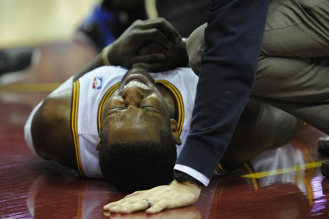 Feb 19, 2014; Cleveland, OH, USA; Cleveland Cavaliers shooting guard C.J. Miles (0) lays on the court with an apparent injury in the fourth quarter against the Orlando Magic at Quicken Loans Arena. Mandatory Credit: David Richard-USA TODAY Sports