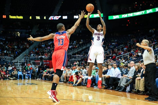 Feb 19, 2014; Atlanta, GA, USA; Atlanta Hawks shooting guard Louis Williams (3) shoots a three over Washington Wizards center Kevin Seraphin (13) in the second half at Philips Arena. The Wizards won 114-97. Mandatory Credit: Daniel Shirey-USA TODAY Sports