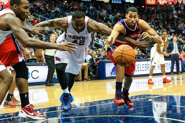 Feb 19, 2014; Atlanta, GA, USA; Atlanta Hawks power forward Elton Brand (42) and Washington Wizards shooting guard Garrett Temple (17) reach for a loose ball in the second half at Philips Arena. The Wizards won 114-97. Mandatory Credit: Daniel Shirey-USA TODAY Sports