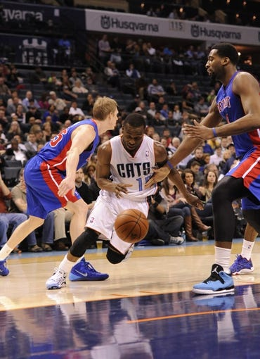 Feb 19, 2014; Charlotte, NC, USA; Charlotte Bobcats guard Kemba Walker (15) moves past the Detroit Pistons defense of Kyle Singler (25) and center Andre Drummond (0) during the second half of the game at Time Warner Cable Arena. Bobcats win 116-98. Mandatory Credit: Sam Sharpe-USA TODAY Sports