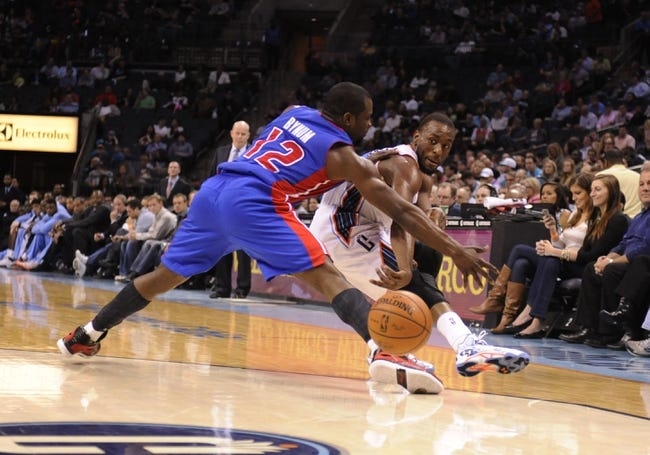 Feb 19, 2014; Charlotte, NC, USA; Charlotte Bobcats guard Kemba Walker (15) passes the ball as he is defended by Detroit Pistons guard Will Bynum (12) during the second half of the game at Time Warner Cable Arena.  Bobcats win 116-98. Mandatory Credit: Sam Sharpe-USA TODAY Sports