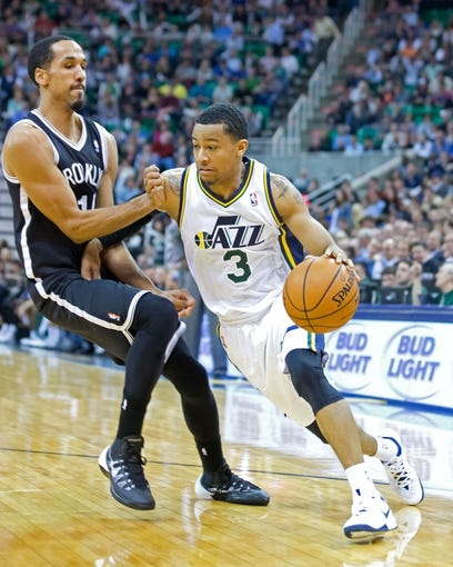 Feb 19, 2014; Salt Lake City, UT, USA; Utah Jazz point guard Trey Burke (3) dribbles the ball around Brooklyn Nets point guard Shaun Livingston (14) during the second half at EnergySolutions Arena. The Nets won 105-99. Mandatory Credit: Russ Isabella-USA TODAY Sports