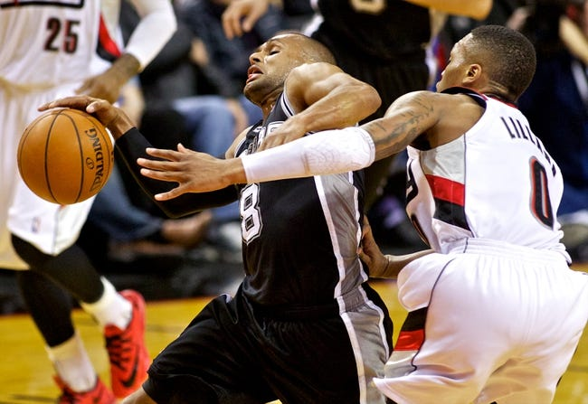 Feb 19, 2014; Portland, OR, USA; San Antonio Spurs point guard Patty Mills (8) is fouled by Portland Trail Blazers point guard Damian Lillard (0) during the third quarter at the Moda Center. Mandatory Credit: Craig Mitchelldyer-USA TODAY Sports