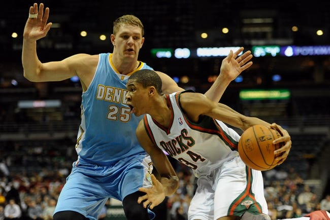 Feb 20, 2014; Milwaukee, WI, USA;  Milwaukee Bucks guard Giannis Antetokounmpo (34) drives for the basket against Denver Nuggets center Timofey Mozgov (25) in the 4th quarter at BMO Harris Bradley Center. The Nuggets beat the Bucks 101-90. Mandatory Credit: Benny Sieu-USA TODAY Sports