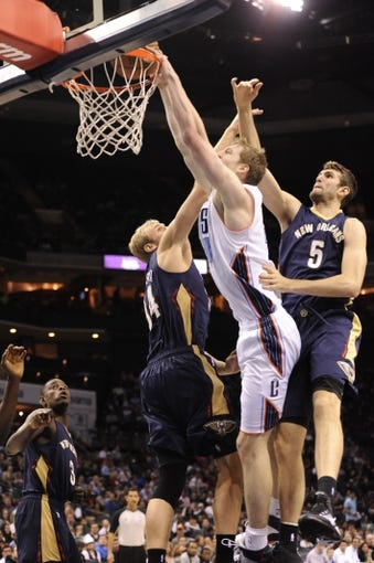 Feb 21, 2014; Charlotte, NC, USA; Charlotte Bobcats center forward Cody Zeller (40) drives to the basket and dunks the ball as he is defended by New Orleans Pelicans center Greg Stiemsma (34) and center Jeff Withey (5) during the first half of the game at Time Warner Cable Arena. Mandatory Credit: Sam Sharpe-USA TODAY Sports
