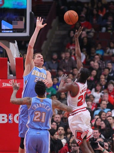 Feb 21, 2014; Chicago, IL, USA; Chicago Bulls shooting guard Tony Snell (20) scores over Denver Nuggets center Timofey Mozgov (25) during the second quarter at the United Center. Mandatory Credit: Dennis Wierzbicki-USA TODAY Sports
