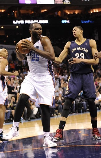 Feb 21, 2014; Charlotte, NC, USA; Charlotte Bobcats center Al Jefferson (25) grabs a rebound in front of New Orleans Pelicans forward center Anthony Davis (23) during the second half at Time Warner Cable Arena. The Bobcats won 90-87. Mandatory Credit: Sam Sharpe-USA TODAY Sports