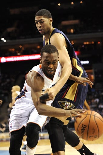 Feb 21, 2014; Charlotte, NC, USA; Charlotte Bobcats guard Kemba Walker (15) gets fouled by New Orleans Pelicans forward center Anthony Davis (23) during the second half at Time Warner Cable Arena. The Bobcats won 90-87.  Mandatory Credit: Sam Sharpe-USA TODAY Sports