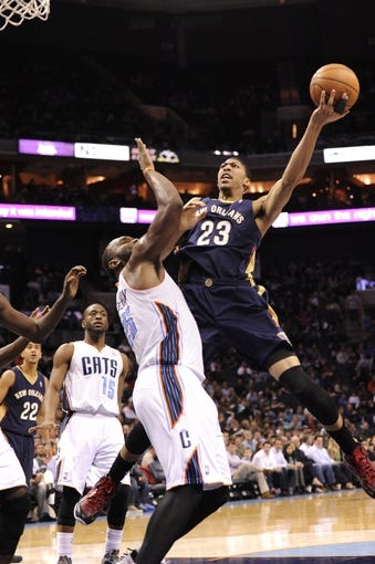 Feb 21, 2014; Charlotte, NC, USA; New Orleans Pelicans forward center Anthony Davis (23) shoots the ball over Charlotte Bobcats center Al Jefferson (25) during the second half at Time Warner Cable Arena. The Bobcats won 90-87. Mandatory Credit: Sam Sharpe-USA TODAY Sports
