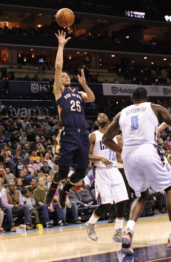 Feb 21, 2014; Charlotte, NC, USA; New Orleans Pelicans guard Austin Rivers (25) takes a shot as he is defended by Charlotte Bobcats guard Kemba Walker (15) and forward center Bismack Biyombo (0) during the second half of the game at Time Warner Cable Arena. Bobcats win 90-87. Mandatory Credit: Sam Sharpe-USA TODAY Sports