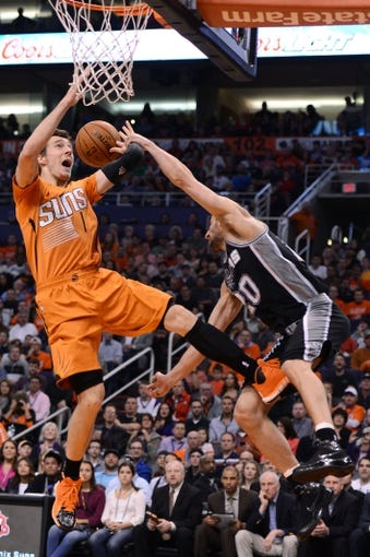 Feb 21, 2014; Phoenix, AZ, USA; Phoenix Suns guard Goran Dragic (1) commits an offensive foul as he goes up with the ball on San Antonio Spurs guard Manu Ginobili (20) in the first half at US Airways Center. Mandatory Credit: Jennifer Stewart-USA TODAY Sports