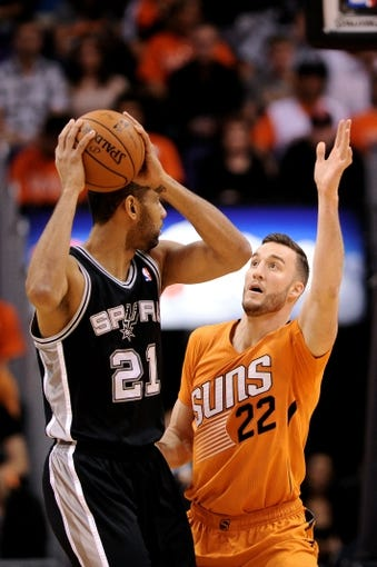 Feb 21, 2014; Phoenix, AZ, USA; Phoenix Suns forward Miles Plumlee (22) defends  San Antonio Spurs forward Tim Duncan (21) in the first half at US Airways Center. Mandatory Credit: Jennifer Stewart-USA TODAY Sports