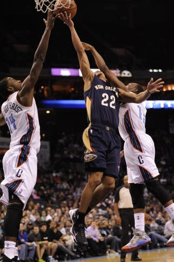 Feb 21, 2014; Charlotte, NC, USA; New Orleans Pelicans guard Brian Roberts (22) drives to the basket as he is defended by Charlotte Bobcats forward Michael Kidd-Gilchrist (14) and guard Kemba Walker (15) during the second half of the game at Time Warner Cable Arena. Bobcats win 90-87. Mandatory Credit: Sam Sharpe-USA TODAY Sports