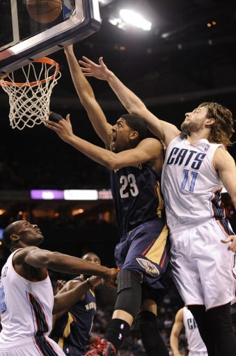Feb 21, 2014; Charlotte, NC, USA; New Orleans Pelicans forward center Anthony Davis (23) drives to the basket as he is defended by Charlotte Bobcats forward Josh McRoberts (11) and forward center Bismack Biyombo (0) during the second half of the game at Time Warner Cable Arena. Bobcats win 90-87. Mandatory Credit: Sam Sharpe-USA TODAY Sports