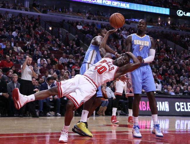 Feb 21, 2014; Chicago, IL, USA; Denver Nuggets power forward Kenneth Faried (35) commits a flagrant foul against Chicago Bulls shooting guard Tony Snell (20) during the second half at the United Center. Chicago won 117-89. Mandatory Credit: Dennis Wierzbicki-USA TODAY Sports