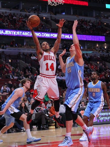 Feb 21, 2014; Chicago, IL, USA; Chicago Bulls point guard D.J. Augustin (14) scores over Denver Nuggets center Timofey Mozgov (25) during the second half at the United Center. Chicago won 117-89. Mandatory Credit: Dennis Wierzbicki-USA TODAY Sports