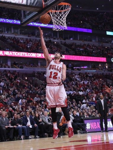 Feb 21, 2014; Chicago, IL, USA; Chicago Bulls shooting guard Kirk Hinrich (12) scores during the second half against the Denver Nuggets at the United Center. Chicago won 117-89. Mandatory Credit: Dennis Wierzbicki-USA TODAY Sports