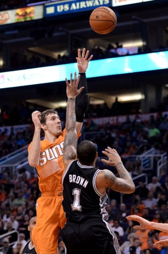Feb 21, 2014; Phoenix, AZ, USA; Phoenix Suns guard Goran Dragic (1) shoots the ball over San Antonio Spurs guard Shannon Brown (1) in the first half at US Airways Center. The Suns won 106-85. Mandatory Credit: Jennifer Stewart-USA TODAY Sports