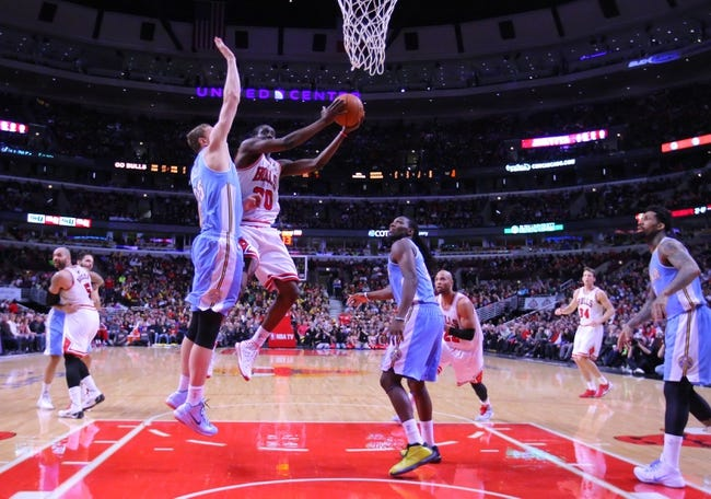 Feb 21, 2014; Chicago, IL, USA; Chicago Bulls shooting guard Tony Snell (20) shoots past Denver Nuggets center Timofey Mozgov (25) during the second half at the United Center. Chicago won 117-89. Mandatory Credit: Dennis Wierzbicki-USA TODAY Sports