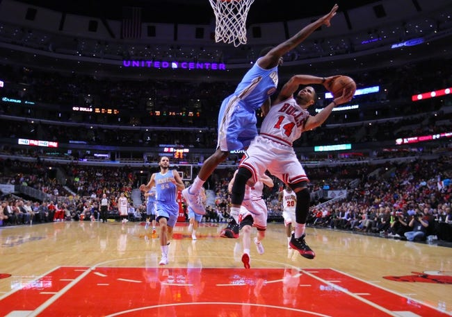 Feb 21, 2014; Chicago, IL, USA; Chicago Bulls point guard D.J. Augustin (14) is fouled by Denver Nuggets point guard Aaron Brooks (0) during the second half at the United Center. Chicago won 117-89. Mandatory Credit: Dennis Wierzbicki-USA TODAY Sports