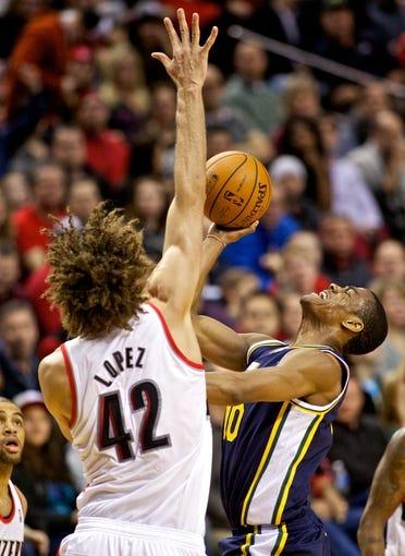 Feb 21, 2014; Portland, OR, USA; Utah Jazz point guard Alec Burks (10) shoots over Portland Trail Blazers center Robin Lopez (42) during the fourth quarter at the Moda Center. Mandatory Credit: Craig Mitchelldyer-USA TODAY Sports