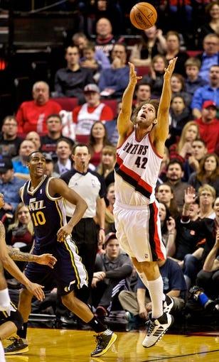 Feb 21, 2014; Portland, OR, USA; Portland Trail Blazers center Robin Lopez (42) grabs a rebound over Utah Jazz point guard Alec Burks (10) during the fourth quarter at the Moda Center. Mandatory Credit: Craig Mitchelldyer-USA TODAY Sports