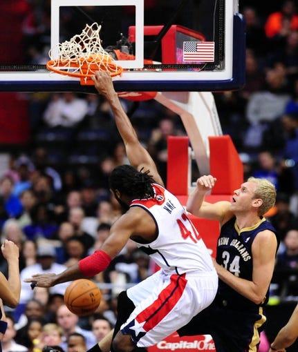 Feb 22, 2014; Washington, DC, USA; Washington Wizards forward Nene (42) dunks the ball over New Orleans Pelicans center Greg Stiemsma (34) in the first quarter at Verizon Center. Mandatory Credit: Evan Habeeb-USA TODAY Sports