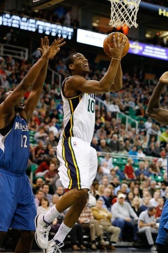 Feb 22, 2014; Salt Lake City, UT, USA; Utah Jazz point guard Alec Burks (10) gets past Minnesota Timberwolves power forward Luc Richard Mbah a Moute (12) and goes to the basket during the fourth quarter at EnergySolutions Arena. Minnesota Timberwolves beat the Utah Jazz 121-104.  Mandatory Credit: Chris Nicoll-USA TODAY Sports