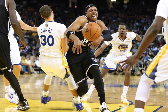 Feb 22, 2014; Oakland, CA, USA; Golden State Warriors point guard Stephen Curry (30) draws a charge against Brooklyn Nets small forward Paul Pierce (34) during the second quarter at Oracle Arena. Mandatory Credit: Kelley L Cox-USA TODAY Sports