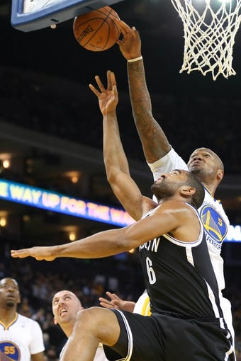 Feb 22, 2014; Oakland, CA, USA; Golden State Warriors power forward Marreese Speights (5) blocks the shot by Brooklyn Nets small forward Alan Anderson (6) during the second quarter at Oracle Arena. Mandatory Credit: Kelley L Cox-USA TODAY Sports