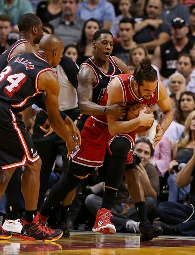 Feb 23, 2014; Miami, FL, USA; Chicago Bulls center Joakim Noah (13) is defended by Miami Heat point guard Mario Chalmers (15) shooting guard Ray Allen (34) and shooting guard Dwyane Wade (3) in the second half at American Airlines Arena. The Heat won 93-79.  Mandatory Credit: Robert Mayer-USA TODAY Sports