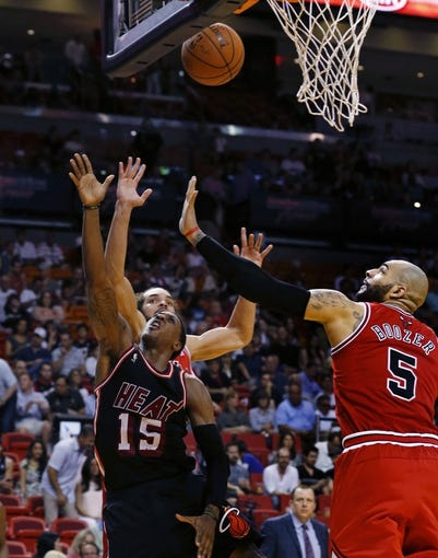 Feb 23, 2014; Miami, FL, USA; Miami Heat point guard Mario Chalmers (15) is defended by Chicago Bulls power forward Carlos Boozer (5) and center Joakim Noah (back) in the second half at American Airlines Arena.The Heat won 93-79.  Mandatory Credit: Robert Mayer-USA TODAY Sports