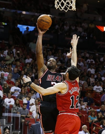 Feb 23, 2014; Miami, FL, USA;  Miami Heat shooting guard Dwyane Wade (3) shoots the ball over Chicago Bulls shooting guard Kirk Hinrich (12) in the second half at American Airlines Arena.The Heat won 93-79.  Mandatory Credit: Robert Mayer-USA TODAY Sports
