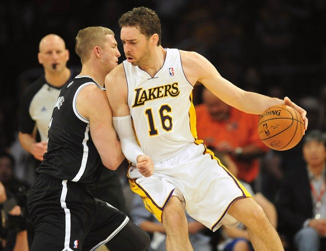 February 23, 2014; Los Angeles, CA, USA; Los Angeles Lakers center Pau Gasol (16) moves the ball against Brooklyn Nets power forward Mason Plumlee (1) during the first half at Staples Center. Mandatory Credit: Gary A. Vasquez-USA TODAY Sports