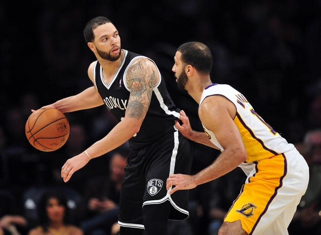February 23, 2014; Los Angeles, CA, USA; Brooklyn Nets point guard Deron Williams (8) controls the ball against Los Angeles Lakers point guard Kendall Marshall (12) during the second half at Staples Center. Mandatory Credit: Gary A. Vasquez-USA TODAY Sports