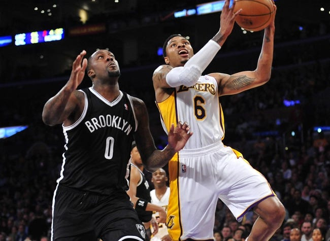 February 23, 2014; Los Angeles, CA, USA; Los Angeles Lakers shooting guard Kent Bazemore (6) moves to the basket against Brooklyn Nets center Andray Blatche (0) during the second half at Staples Center. Mandatory Credit: Gary A. Vasquez-USA TODAY Sports