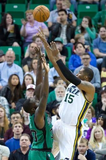 Feb 24, 2014; Salt Lake City, UT, USA; Utah Jazz center Derrick Favors (15) shoots the ball over Boston Celtics power forward Brandon Bass (30) during the first half at EnergySolutions Arena. Mandatory Credit: Russ Isabella-USA TODAY Sports