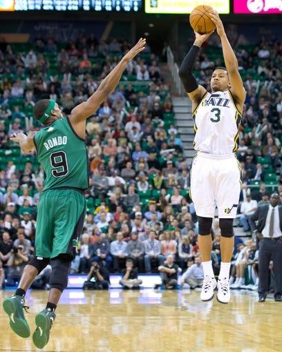 Feb 24, 2014; Salt Lake City, UT, USA; Utah Jazz point guard Trey Burke (3) shoots the ball over Boston Celtics point guard Rajon Rondo (9) during the second half at EnergySolutions Arena. The Jazz won 110-98. Mandatory Credit: Russ Isabella-USA TODAY Sports