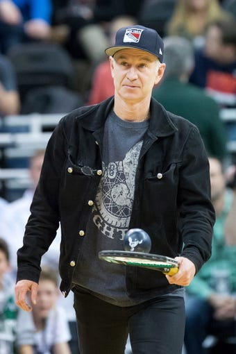Feb 24, 2014; Salt Lake City, UT, USA; Tennis star John McEnroe serves souvenirs to the crowd during the first half between the Utah Jazz and the Boston Celtics at EnergySolutions Arena. The Jazz won 110-98. Mandatory Credit: Russ Isabella-USA TODAY Sports