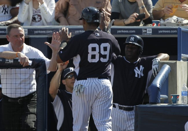 Feb 25, 2014; Tampa, FL, USA; New York Yankees second baseman Yangervis Solarte (89) is congratulated by teammates after he scored a run during the fourth inning against the Florida State Seminoles at George M. Steinbrenner Field. Mandatory Credit: Kim Klement-USA TODAY Sports