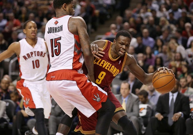 Feb 21, 2014; Toronto, Ontario, CAN; Cleveland Cavaliers forward Luol Deng (9) tries to get past Toronto Raptors forward Amir Johnson (15) at Air Canada Centre. The Raptors beat the Cavaliers 98-91. Mandatory Credit: Tom Szczerbowski-USA TODAY Sports