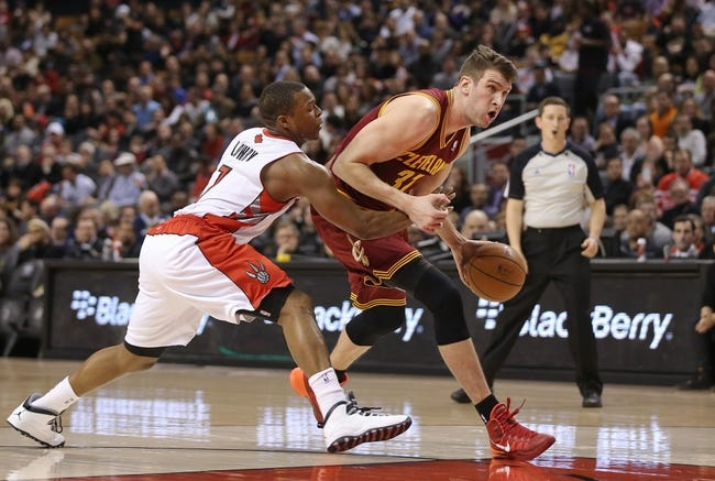Feb 21, 2014; Toronto, Ontario, CAN; Cleveland Cavaliers center Spencer Hawes (32) goes to the basket as Toronto Raptors point guard Kyle Lowry (7) defends at Air Canada Centre. The Raptors beat the Cavaliers 98-91. Mandatory Credit: Tom Szczerbowski-USA TODAY Sports